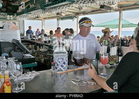 Male bartender behind the bar at the busy rooftop bar and restaurant or grill of Bud and Alley's in the Florida panhandle beach town of Seaside, USA. - Stock Image