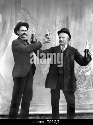 Two early twentieth century men toast each other with beer bottles for a studio portrait, ca. 1905. - Stock Image