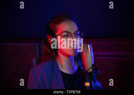 A young pretty woman in glasses singing in neon lighting - Stock Image