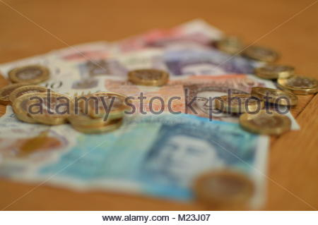 British pound sterling notes and new one pound coins stacked together on wooden table. - Stock Image