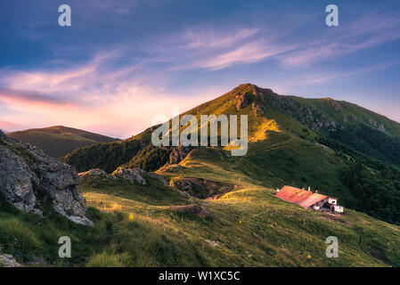 Idyllic landscape in the Old mountain, Central Balkan national park in Bulgaria. Eho hut surrounded with fresh green mountain pastures with blooming f - Stock Image