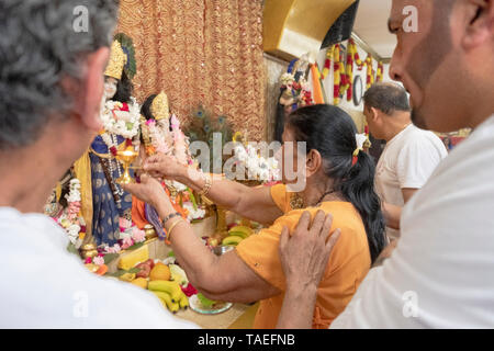 A Hindu woman in her late seventies offers fire to the deities as an act of appreciation for the good things in her life. In Ozone Park, Queens, NYC. - Stock Image
