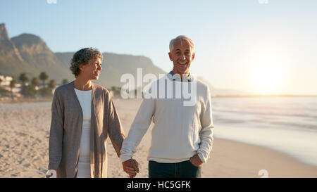 Outdoors shot of happy mature couple strolling on the beach. Senior man and senior woman taking a walk on the sea - Stock Image