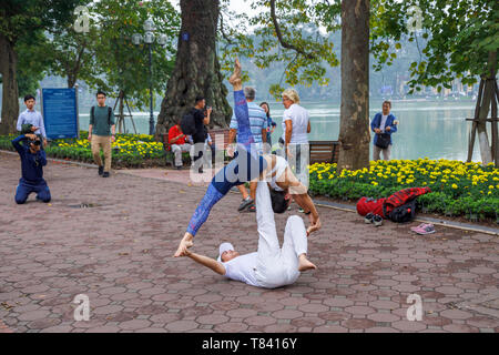 A young couple perform acrobatics on the pavement on the side of Hoan Kiem Lake in the historic centre of Hanoi, north Vietnam, south-east Asia - Stock Image