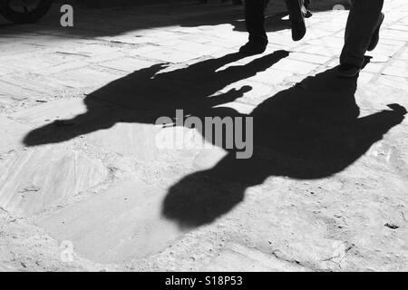 Shadows of men walking - Stock Image
