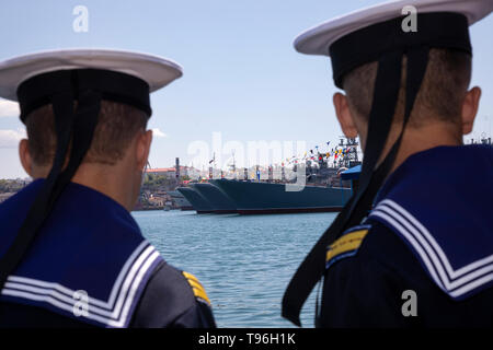 Sailors look at the decorated warships of the Black Sea fleet of the Russian Navy on in the Bay of Sevastopol, Crimea - Stock Image