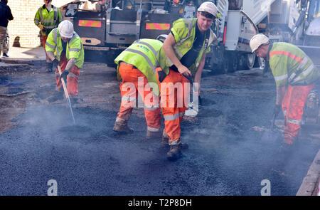 Team of workmen shovelling, spreading hot tarmac on city road repair job, England, UK - Stock Image