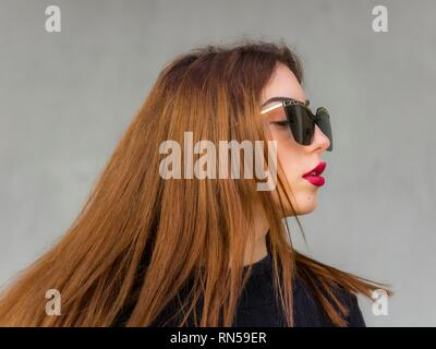 Pretty teen girl blonde spread hair portrait with sunglasses looking away aside serious - Stock Image