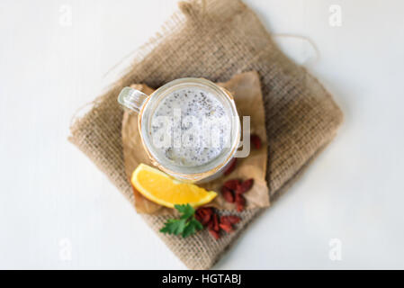 Chia seed pudding in a jar on white wooden background - Stock Image