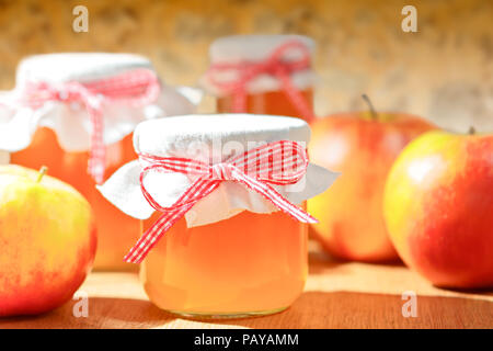 Homemade apple jelly in glass jars with linen cover and a nostalgic ribbon bow in bright sunshine in front of an old stone wall - Stock Image