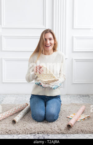 Woman sitting on rug with variety of fabrics - Stock Image