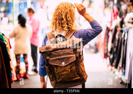 Blonde curly hair woman backpacker traveler viewed from rear at used market enjoying the shopping and alternative vacation - leather backpack view for - Stock Image