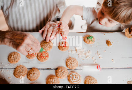 A midsection of senior grandmother with small toddler boy making and decorating cakes at home. A top view. - Stock Image