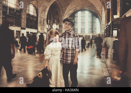 Two young vintage traveller children are standing in an old train station waiting for transportation for an imagination - Stock Image