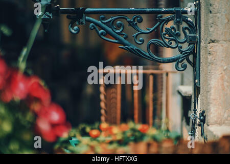 Fragment of base of old black metal toreutic lantern with blurred rusty balcony behind and red flowers in front, - Stock Image
