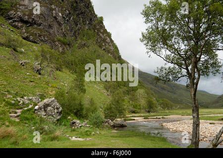Looking along the rocky shores of the Water of Nevis in Glen Nevis with the lower slopes of Meall Cumhann on the - Stock Image