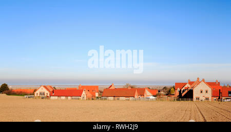 A view of a modern housing estate built in traditional local style in North Norfolk on the outskirts of Blakeney, Norfolk, England, UK Europe. - Stock Image