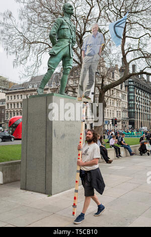 An image of veteran wildlife and environmental broadcaster Sir David Attenborough is held high in Parliament Square next to the statue of Field Marshal Jan Christiaan Smuts, the South African and British Commonwealth statesman, military leader and philosopher, during the week-long protest by climate change activists with Extinction Rebellion's campaign to block road junctions and bridges around the capital, on 23rd April 2019, in London England. - Stock Image
