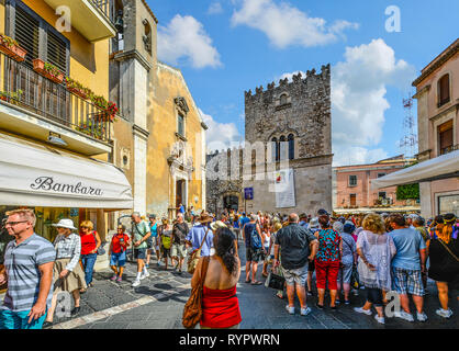 A crowd of tourists gathers in front of Saint Catherine church on piazza Badia in the coastal village of Taormina, Italy - Stock Image