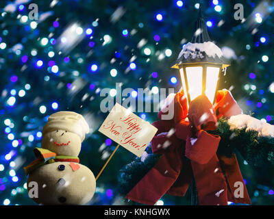 """Snowman figure holding a placard board. Text """"Happy New Year!"""". Street lantern wrapped in red ribbon and fir branches. - Stock Image"""