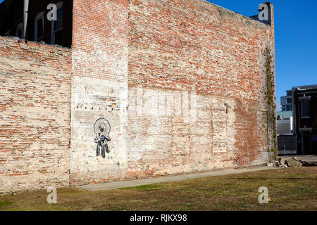 Likeness of Dr Martin Luther King Jr (MLK) painted on the side of an old brick wall in a vacant lot in downtown Montgomery Alabama, USA. - Stock Image