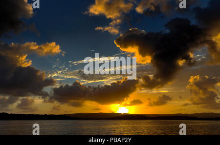 A spectacular inspirational brightly coloured Cumulonimbus cloudy sea water tropical panoramic sunrise seascape featuring silhouettes - Stock Image