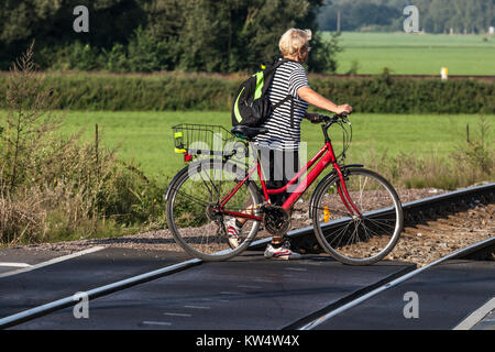 Cyclist Woman with bicycle crosses the railway crossing - Stock Image