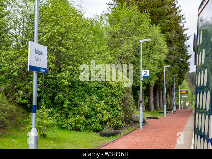 Tulloch rural train station platform with name sign and ScotRail train on West Highland railway line, Scottish Highlands, Scotland, UK - Stock Image