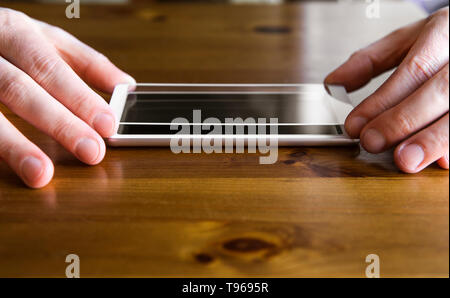 Man hands fingers hold smartphone screen protective covering glass on top of smartphone, about to install the protection glass. Protecting from scatte - Stock Image