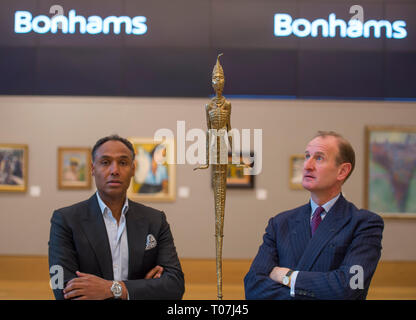 Bonhams, New Bond Street, London, UK. 18 March, 2019. Leading the sale, which takes place on 20 March 2019, are works by Benedict Chukwukadibia Enwonwu and Gerard Sekoto. Image: Costume Designer and Creative Director Roubi L'Roubi (left) has curated a section of the African Art sale, seen here with Giles Peppiatt (right), Director, Modern & Contemporary African Art, Bonhams, viewing Ben Enwonwu's sculpture, Anyanwu, which has an estimate of £100,000-150,000. Credit: Malcolm Park/Alamy Live News. - Stock Image