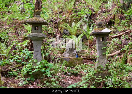 Japanese stone lanterns near Towada shinto shrine in Aomori prefecture, Japan. Traditionally, alcohol is left at the spot as a offer to the gods. - Stock Image