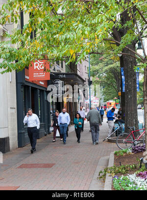 CHARLOTTE, NC, USA-10/30/18: Smiling people walk to lunch; one man talks on cellphone. - Stock Image