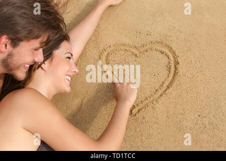 Happy couple in love lying and drawing a heart on the sand of the beach - Stock Image