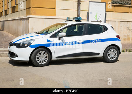 Italy Sicily Agrigento modern police car white blue stripe Polizia Locale Renault Clio blue lights parked cobble cobbled street road - Stock Image