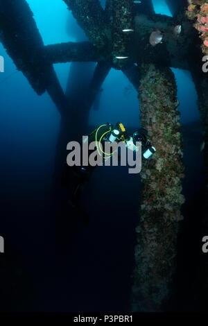 Diving under an oil platform - Stock Image
