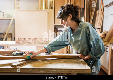 Young woman sanding wood in a workshop - Stock Image