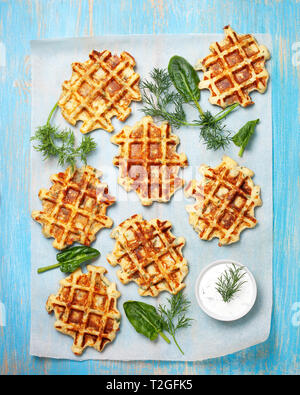 healthy breakfast. savory  spinach dill waffles, with tzatziki on a blue background. view from above - Stock Image
