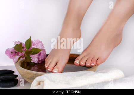 Female legs and feet with french nails polish in spa studio with wooden bowl with water and decoration pink flower and black rock. Pedicure and health - Stock Image