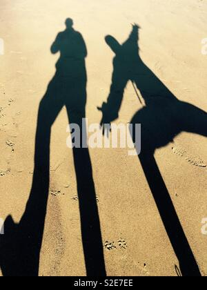 Two figures creating shadows on the beach - Stock Image