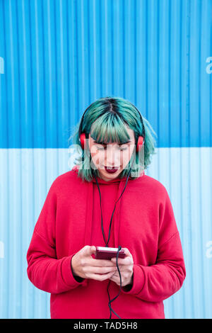 Portrait of young woman with blue dyed hair listening music with headphones looking at smartphone - Stock Image