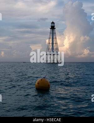 Alligator Light at dawn with a marker buoy in the foreground. - Stock Image