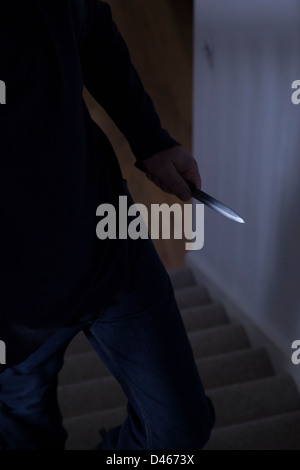 Shadowy male intruder holding a knife. - Stock Image