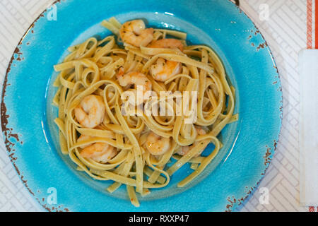Shrimp scampi over fetticchini pasta served on an aqua plate. From above. - Stock Image
