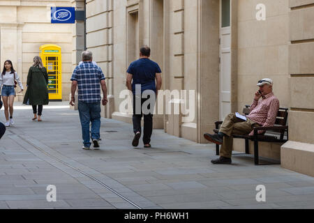 Gentleman sitting on a bench talking on a mobile phone with passersby coming and going and a yellow defibrillator phone box in the background - Stock Image