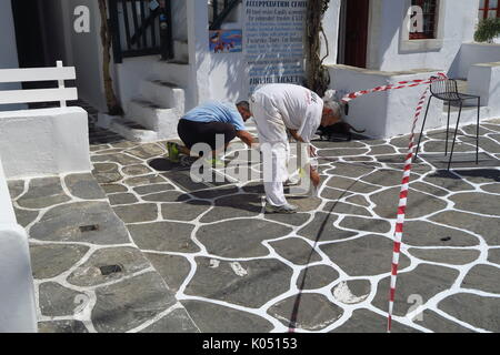 Workmen painting white lines between paving stones on the Greek island of Mykonos - Stock Image