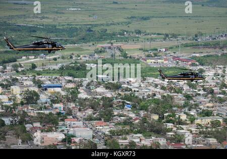 U.S. Army UH-60 Black Hawk helicopters fly over the solar and wind farms damaged by Hurricane Maria during relief - Stock Image