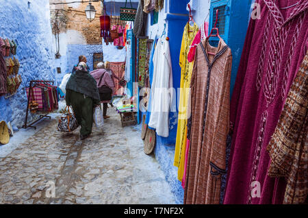 Chefchaouen, Morocco : Two women walk past traditional clothing stores in the blue-washed medina old town. - Stock Image