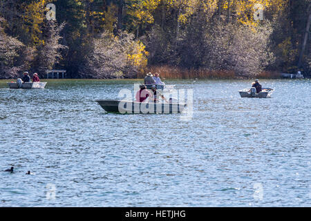 Fishermen in a small boat on Gull Lake with trees in fall color in the eastern Sierra Nevada mountains on the June - Stock Image