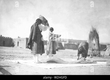 Edward S. Curtis Native American Indians - Tewa Indians winnowing wheat, San Juan, New Mexico - Stock Image