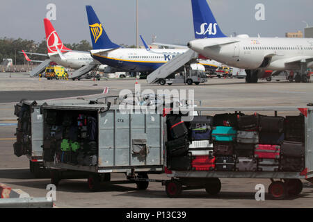 Luggage trolleys waiting to be towed to an aircraft on the apron at Malta International Airport. Baggage handling and air travel at a busy airport. - Stock Image
